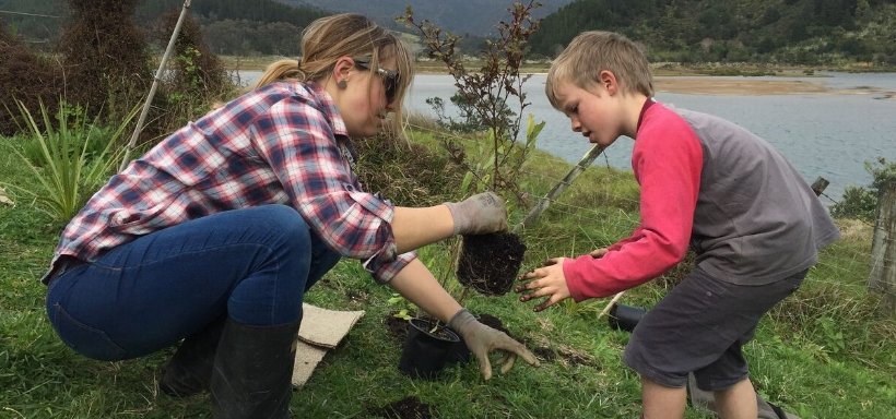 Natalie helps a child plant a tree in the MEG Childrens forest